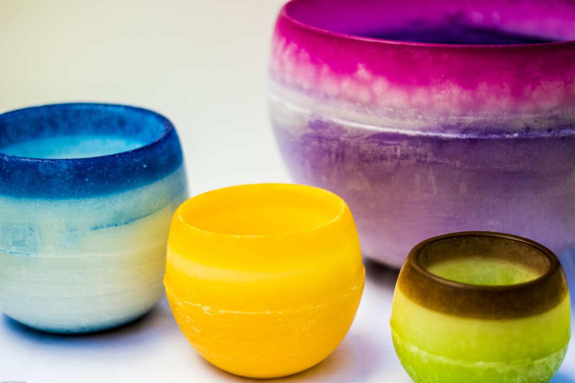 Cuatro cuencos de parafina de distintos tamaños y colores azul amarillo verde y lila