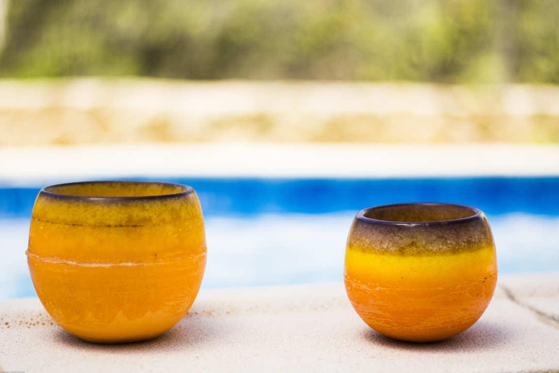 Dos cuencos de parafina color naranja sobre bordillo de piscina