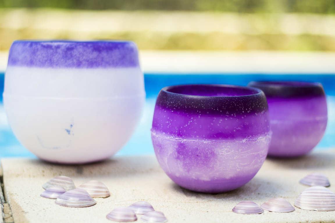 Tres cuencos de parafina de aroma lavanda color lila sobre bordillo de piscina rodeados de conchas rosadas