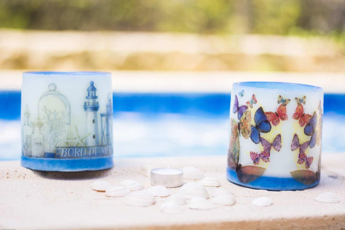 Dos cuencos de parafina azules con dibujos sobre bordillo de piscina rodeados de conchas blancas