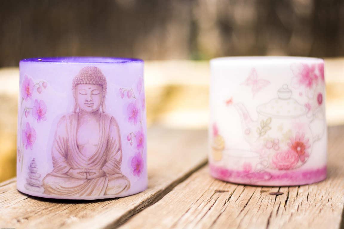 Dos cuencos de parafina color lila y rosa con dibujos sobre banco de madera con plantas de fondo