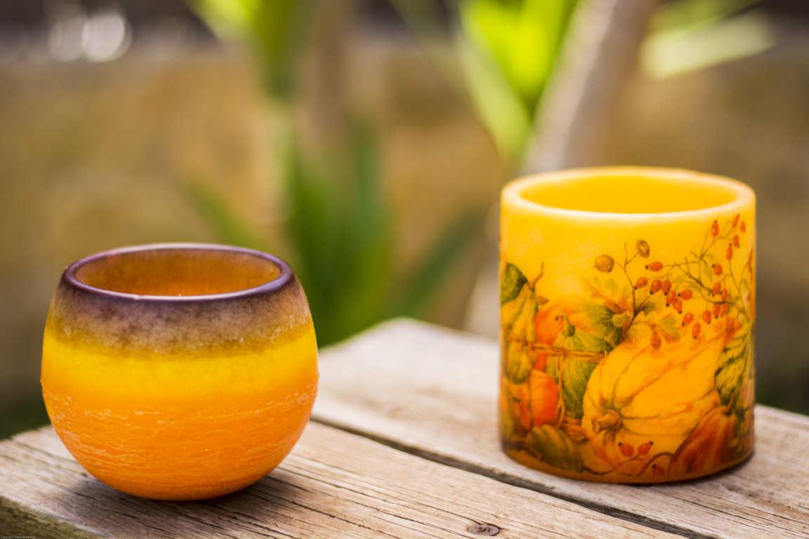 Dos cuencos de parafina color naranja y marrón sobre banco de madera con plantas de fondo