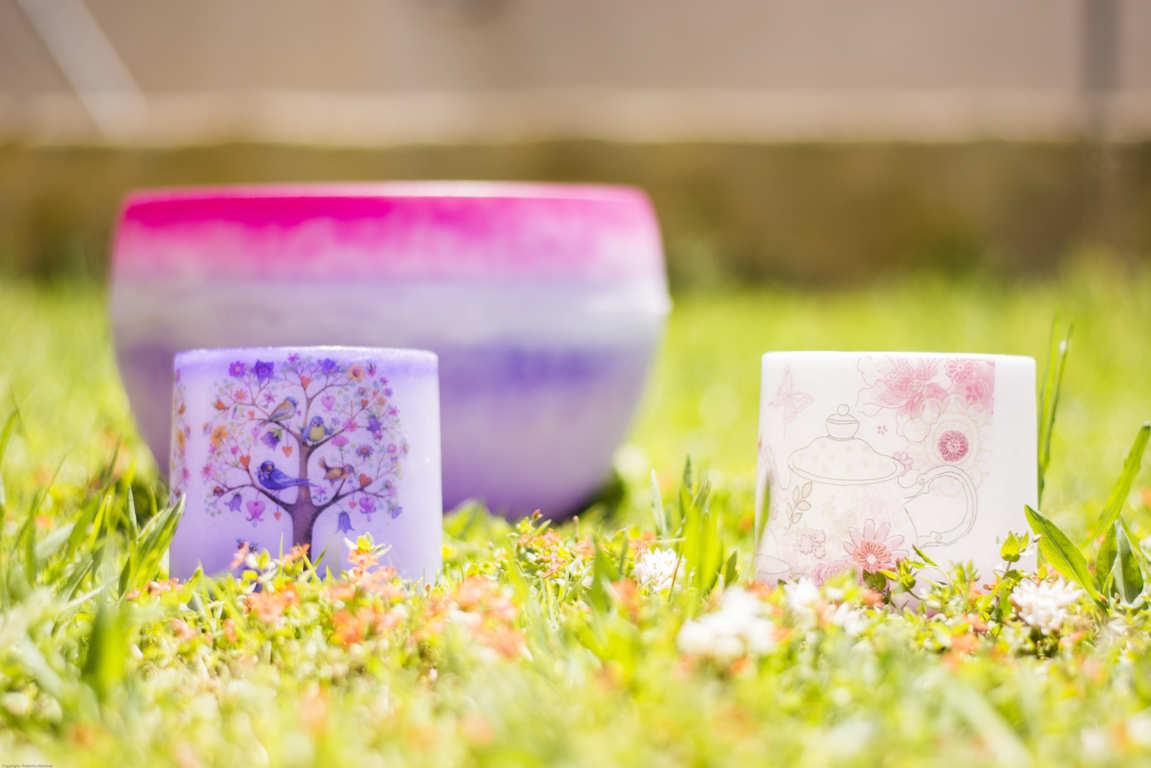 Tres cuencos de parafina de diferentes tamaños colores lila y rosa sobre la hierva