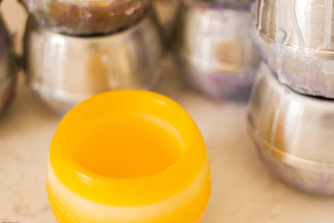 Cuenco redondo de parafina color amrillo moldes metálicos redondos apilados en mesa de trabajo artesanal