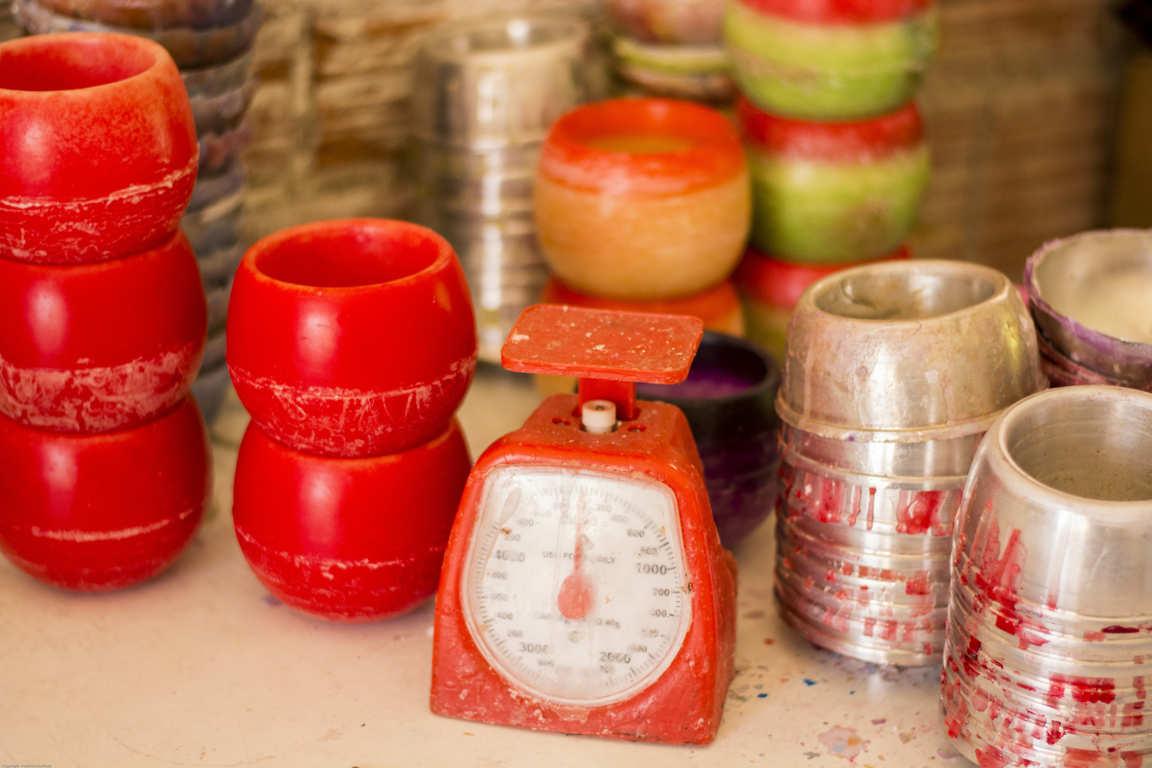 Báscula color roja moldes de metal circulares cuencos de parafina apilados sobre mesa de taller de fabricación de cuencos aromáticos
