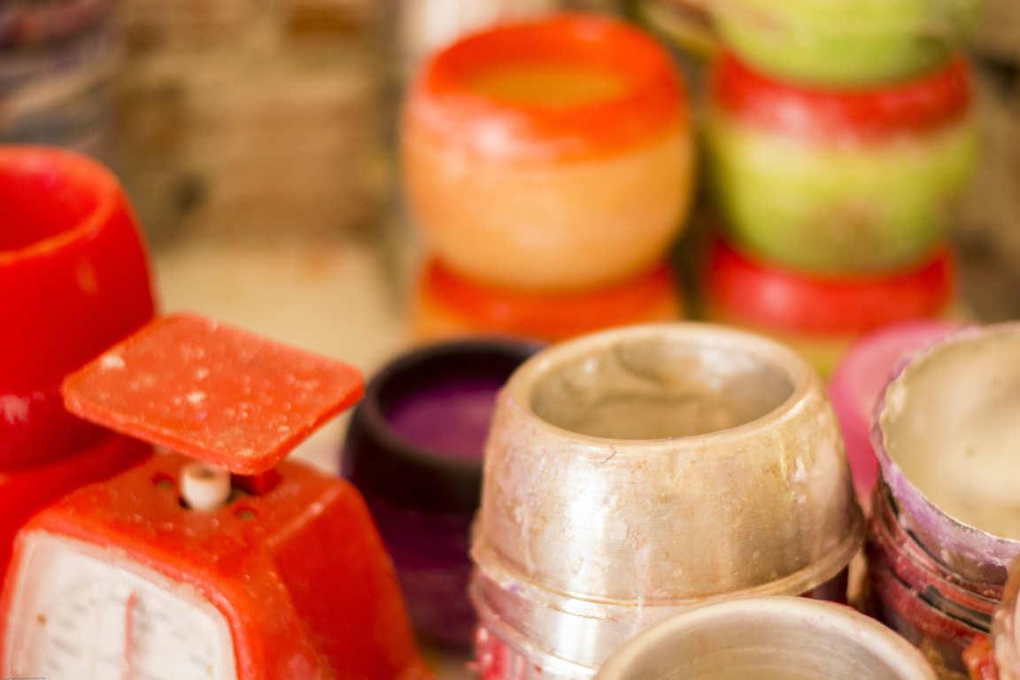 Moldes metálicos circulares y cuencos de parafina apilados báscula roja sobre mesa de taller de elaboración de cuencos de parafina