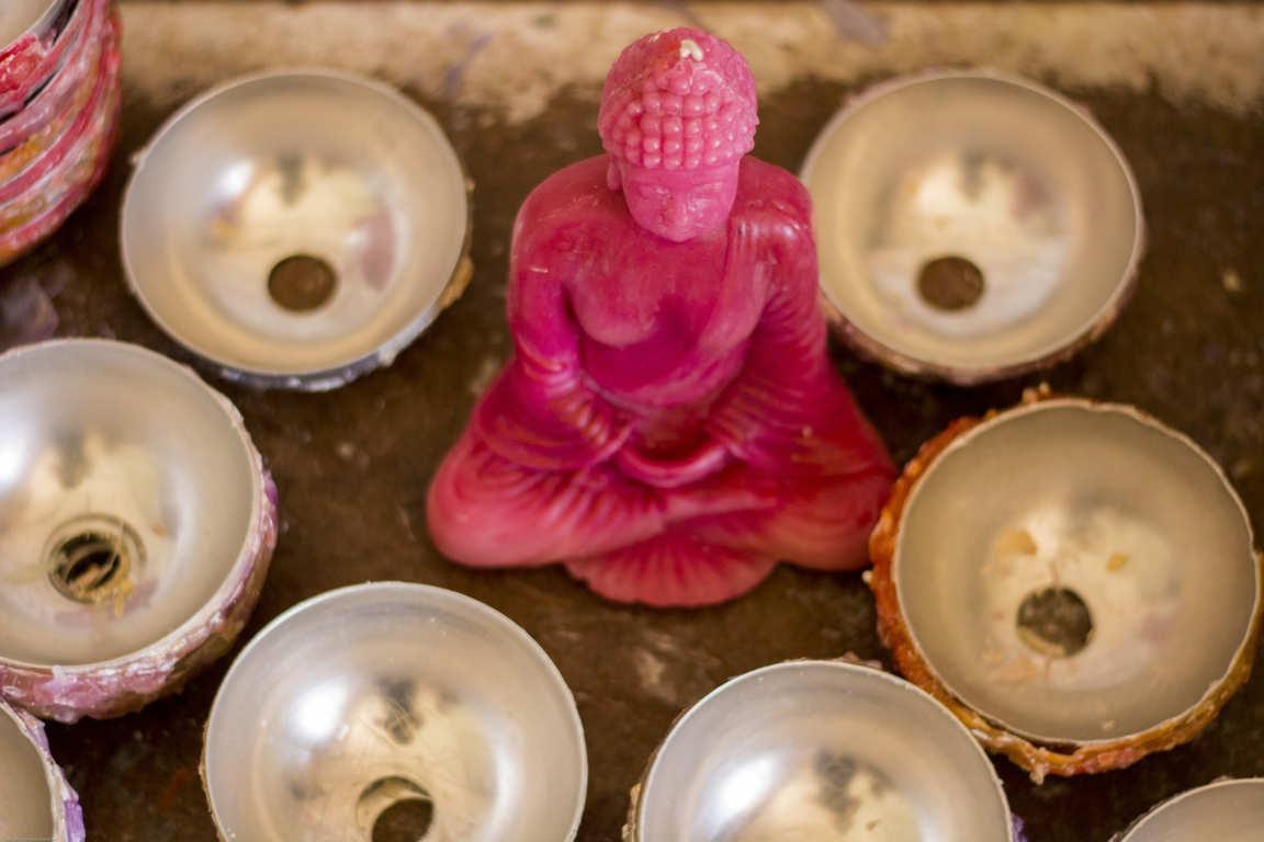 Vista superior de moldes metálicos circulares en mesa de taller de fabricación de cuencos de parafina y vela de buda rosa