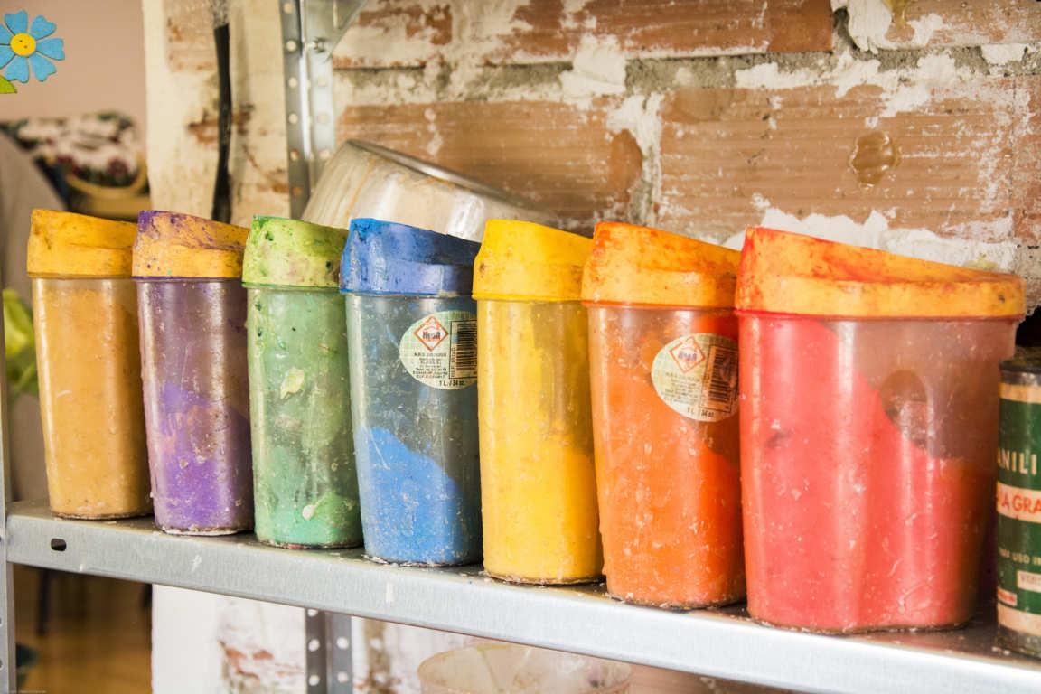 Estante con botes que contienen pigmentos de colores para fabricación de cuencos de parafina