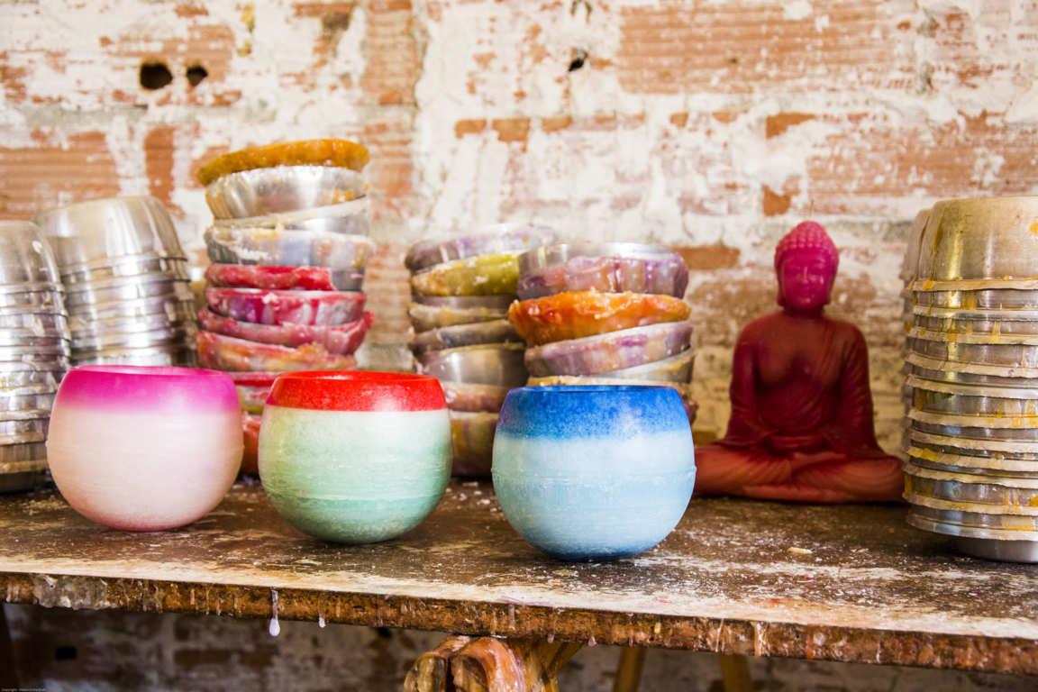 Mesa de trabajo de taller artesanal con tres cuencos de parafina moldes de fabricación y figura de velade buda color roja