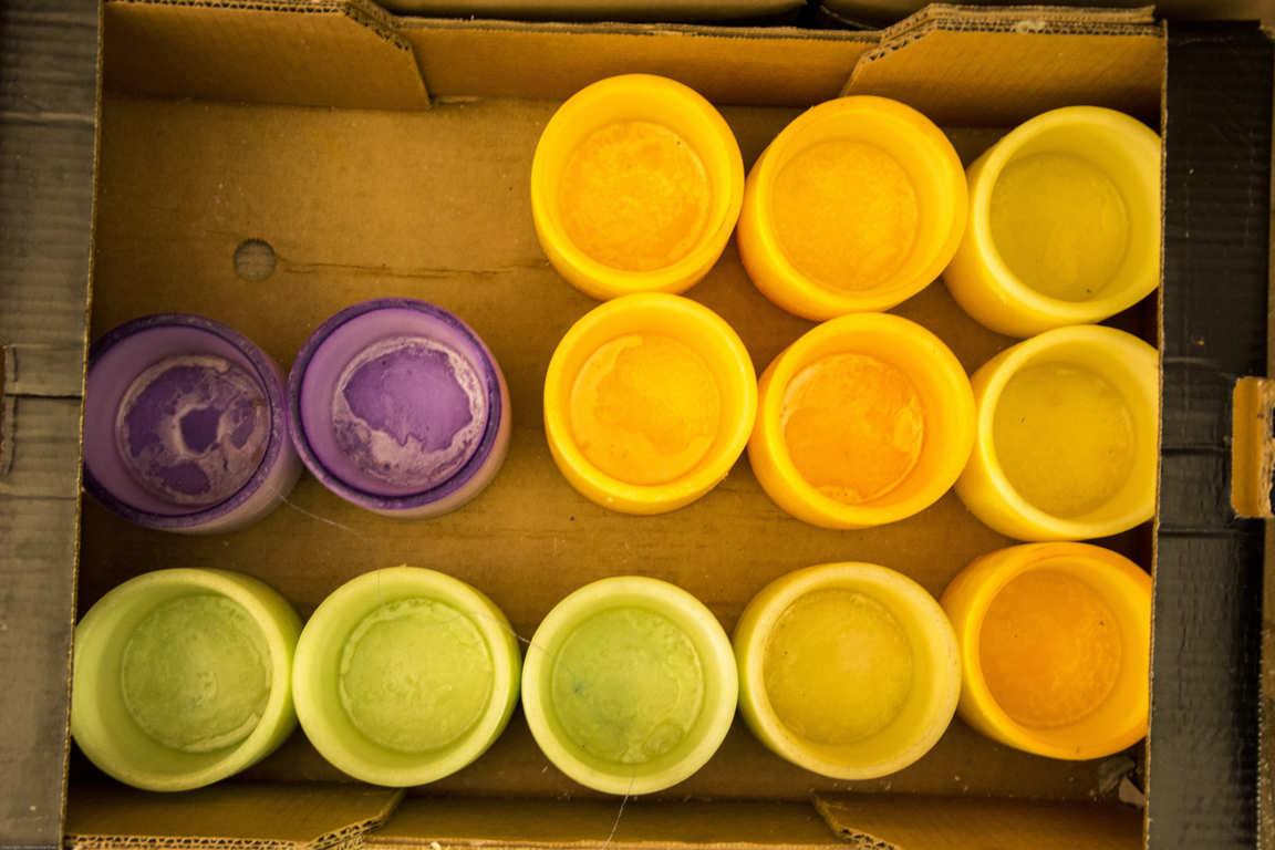 Vista superior de caja con cuencos de parafina de colores lila verde y naranja