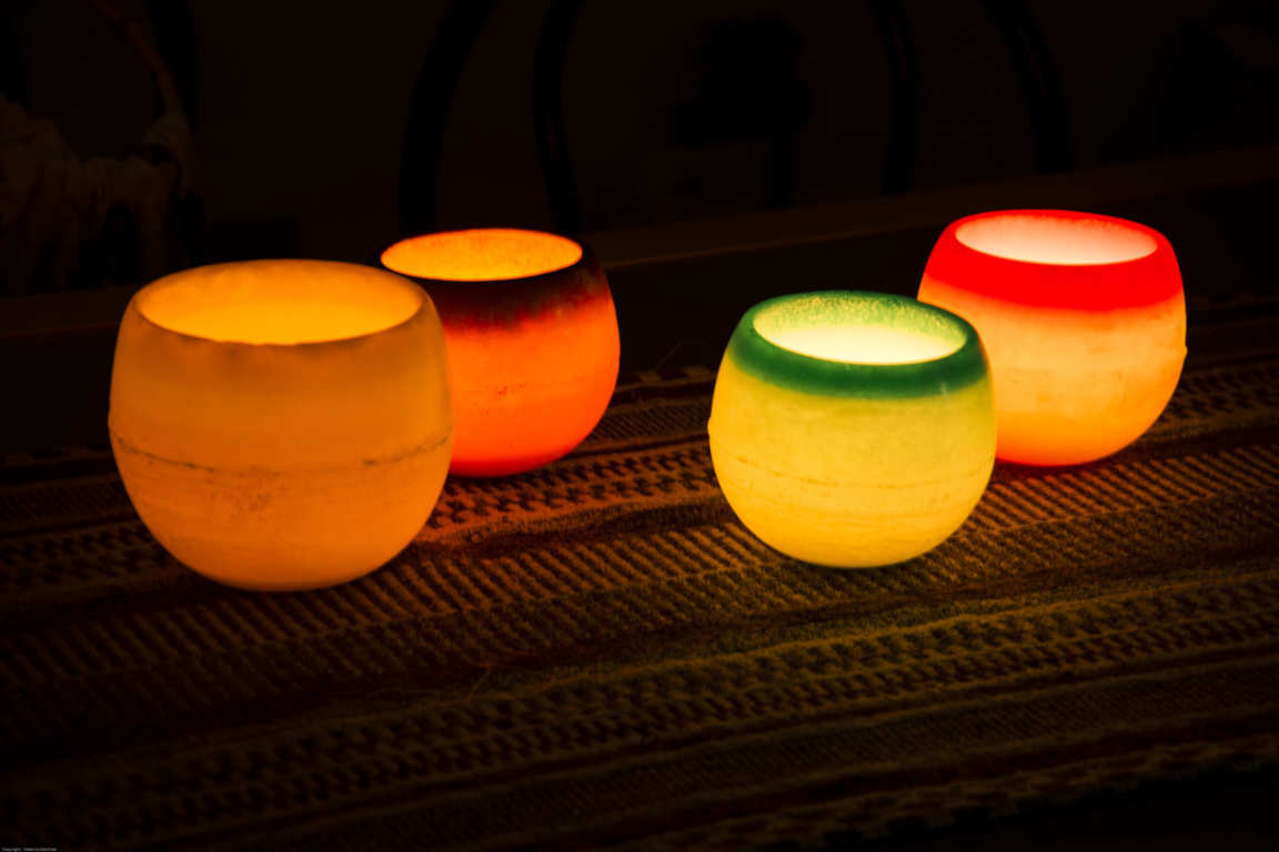 Cuatro cuencos de parafina iluminados con vela interior en ambiente oscuro