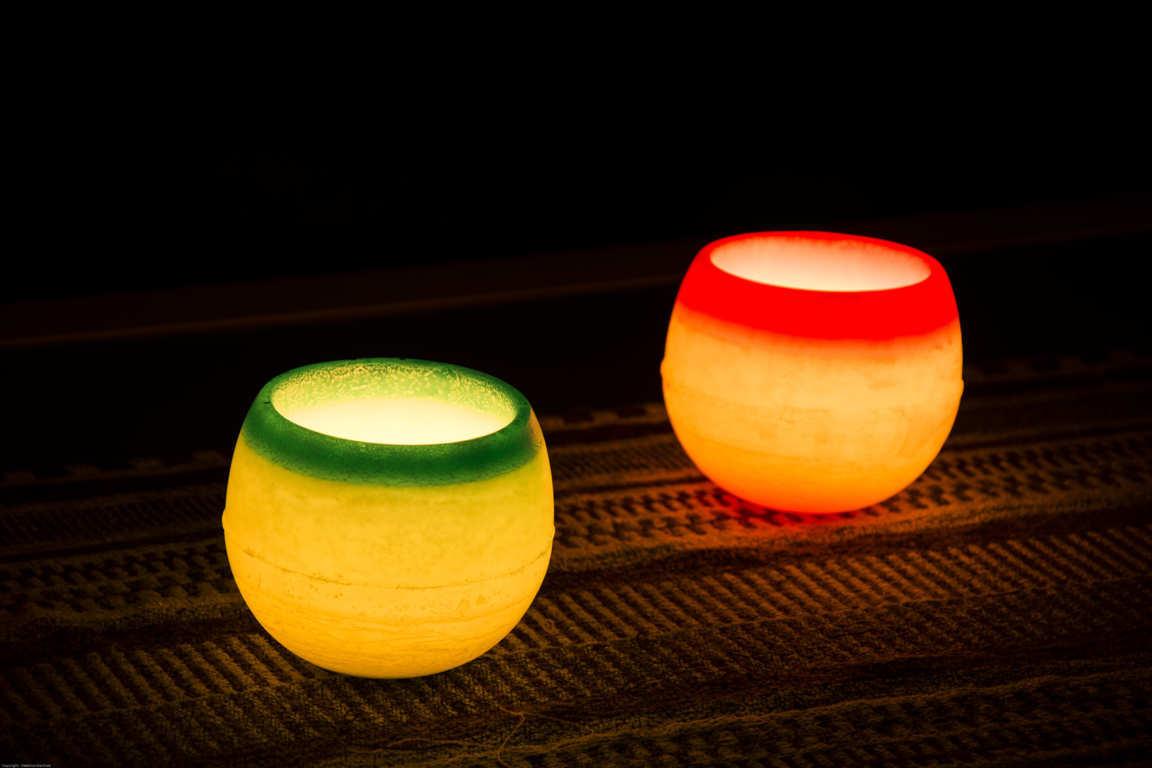 Dos cuencos de parafina verde y rojo iluminados con vela interior en ambiente oscuro
