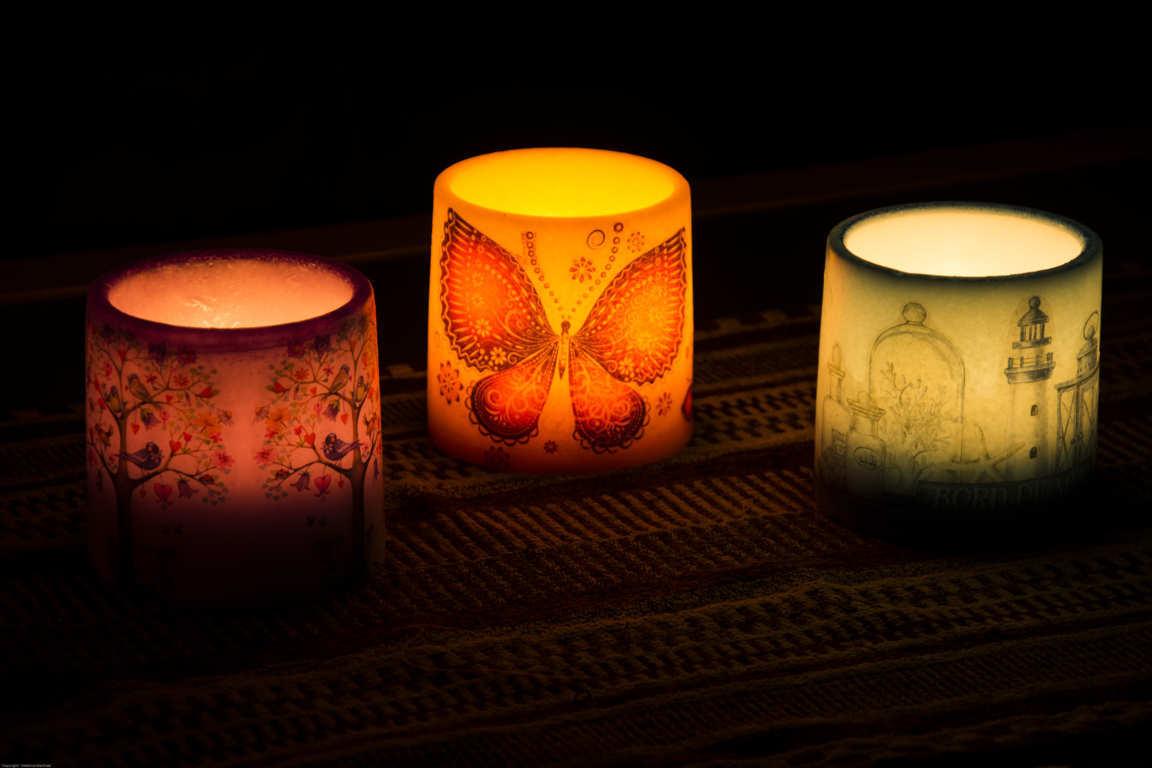 Tres cuencos con dibujos iluminados con una vela interior en ambiente oscuro